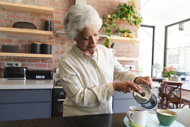 Senior retired African American woman at home standing in the kitchen, carefully pouring a mug of coffee from a cafetiere, at home isolating during coronavirus covid19 pandemic