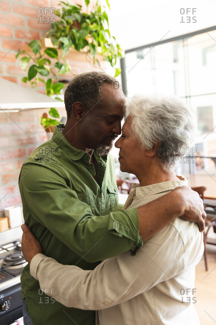 Side view of a happy senior retired African American couple at home standing in their kitchen, touching heads together and looking at each other while embracing, at home together isolating during coronavirus covid19 pandemic