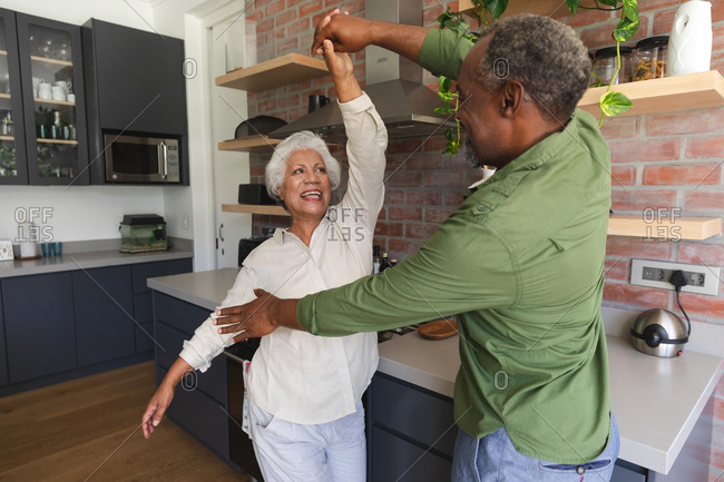 Happy senior retired African American couple at home holding hands, dancing together and smiling in their kitchen, at home together isolating during coronavirus covid19 pandemic