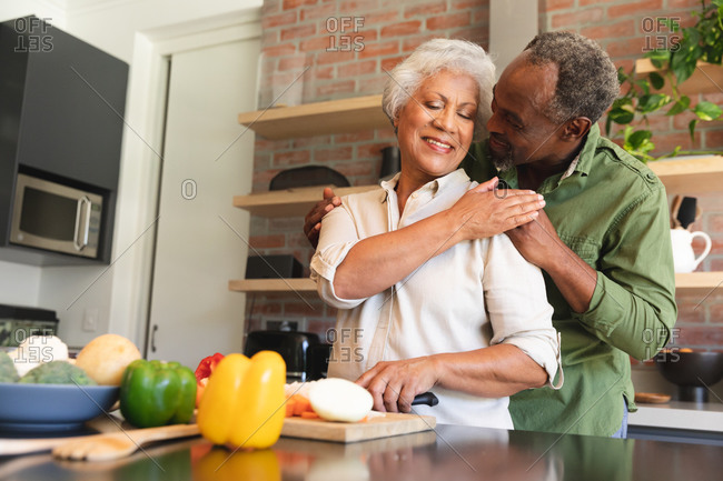 Happy senior retired African American couple at home, preparing food, cutting vegetables, and embracing in their kitchen, at home together isolating during coronavirus covid19 pandemic