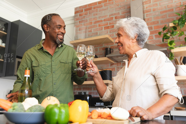 Happy senior retired African American couple at home, preparing vegetables to make a meal, and making a toast with glasses of white wine, couple at home together isolating during coronavirus covid19 pandemic