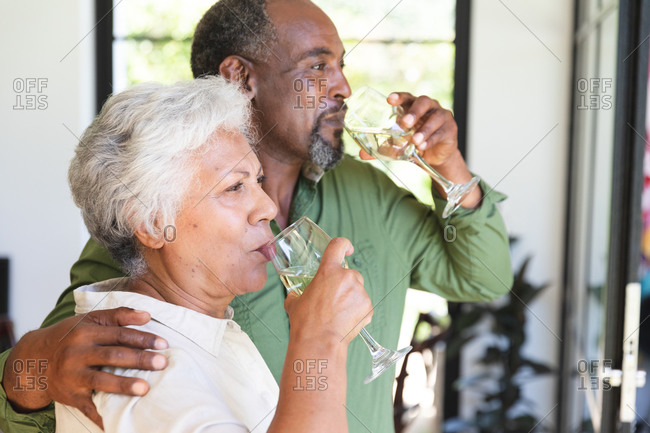 Happy senior retired African American couple at home, embracing and drinking glasses of white wine, couple at home together isolating during coronavirus covid19 pandemic