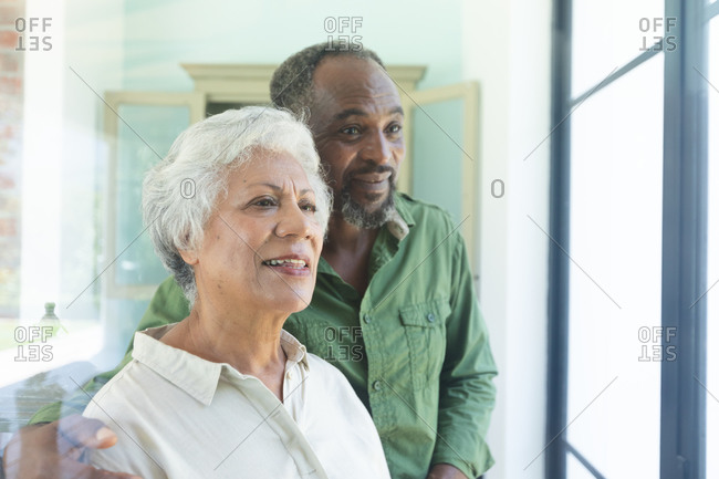 Happy senior retired African American couple at home, embracing and smiling while looking out of the window, couple at home together isolating during coronavirus covid19 pandemic