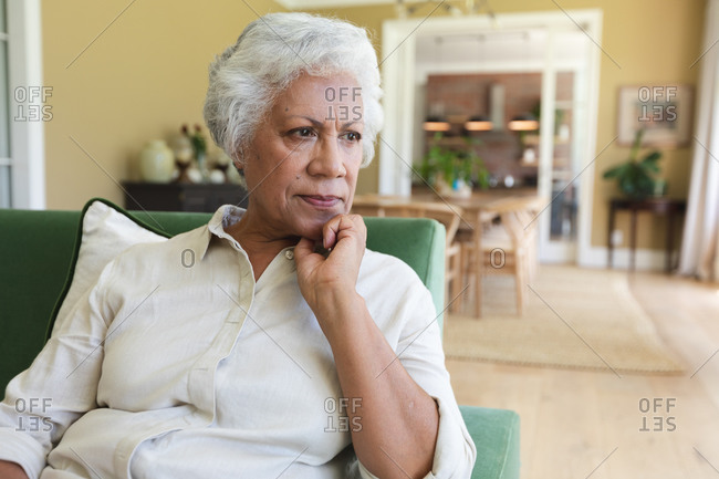Close up of happy senior retired African American woman at home sitting in her living room, leaning on her hand and thinking, self isolating during coronavirus covid19 pandemic