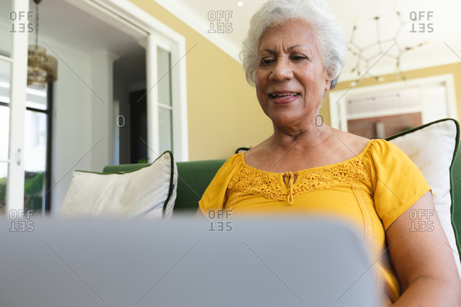Close up of a happy attractive senior retired African American woman at home sitting in an armchair in her living room, using a laptop computer and smiling, self isolating during coronavirus covid19 pandemic