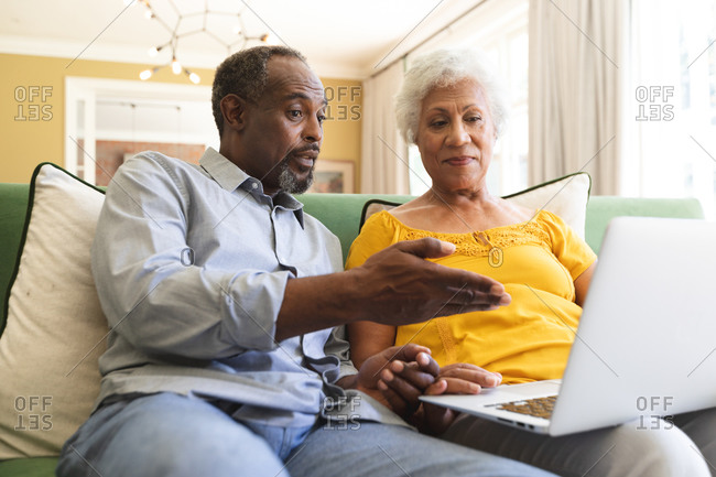 Close up of a happy senior retired African American couple at home sitting on a sofa in their living room, talking and using a laptop computer together and smiling, couple isolating during coronavirus covid19 pandemic