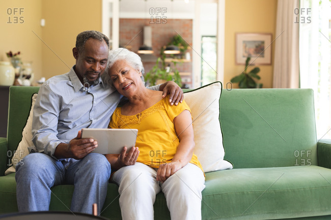 Happy senior retired African American couple at home sitting on a sofa in their living room, embracing and using a tablet computer together and smiling, couple isolating during coronavirus covid19 pandemic