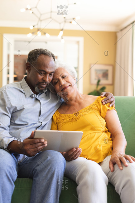 Close up of a happy senior retired African American couple at home sitting on a sofa in their living room, embracing and using a tablet computer together and smiling, couple isolating during coronavirus covid19 pandemic