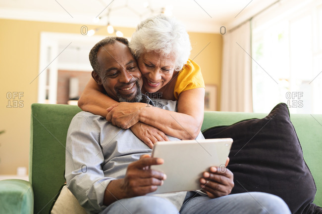 Happy senior retired African American couple at home, the man sitting on a sofa in their living room, the woman standing behind and embracing him, looking at a tablet computer together and smiling, couple isolating during coronavirus covid19 pandemic