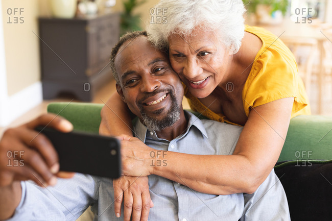 Close up of a happy senior retired African American couple at home in their living room, the man sitting on a sofa holding a smartphone the woman standing behind and embracing him, looking at the phone together, taking a selfie and smiling, couple isolating during coronavirus covid19 pandemic