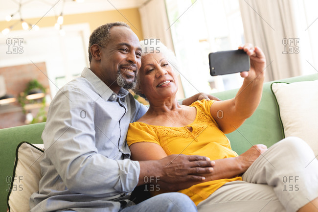 A happy senior retired African American couple at home in their living room, sitting on a sofa, the woman holding a smartphone, both looking at the phone together, taking a selfie and smiling, couple isolating during coronavirus covid19 pandemic