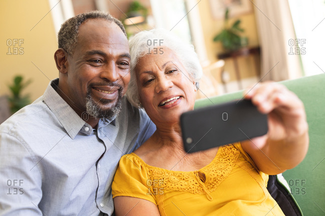 Close up of a happy senior retired African American couple at home in their living room, sitting on a sofa, the woman holding a smartphone, both looking at the phone together, taking a selfie and smiling, couple isolating during coronavirus covid19 pandemic