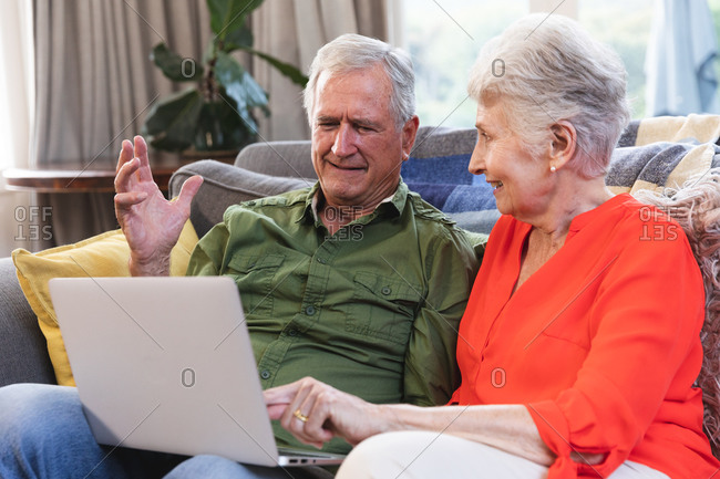 A retired senior Caucasian couple at home sitting on a sofa in their living room, talking and smiling, using a laptop computer together, couple isolating during coronavirus covid19 pandemic