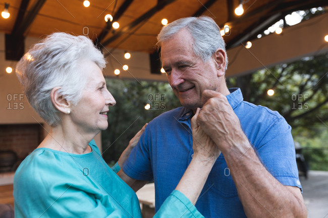 Happy retired senior Caucasian couple at home holding hands, dancing together and smiling, at home together isolating during coronavirus covid19 pandemic