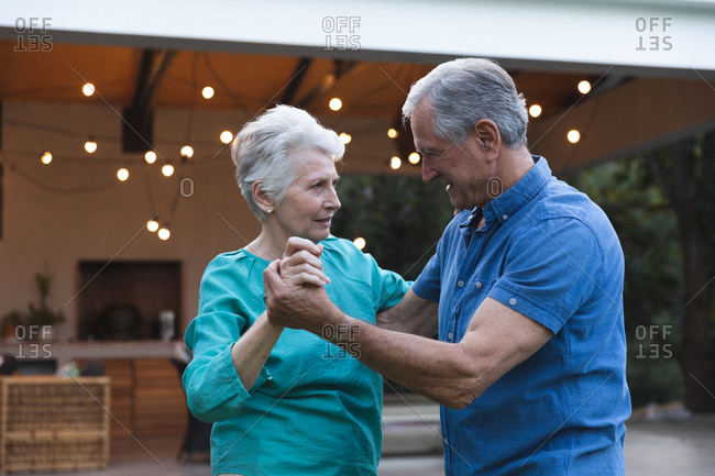 Happy retired senior Caucasian couple at home holding hands, dancing together in their garden and smiling, at home together isolating during coronavirus covid19 pandemic