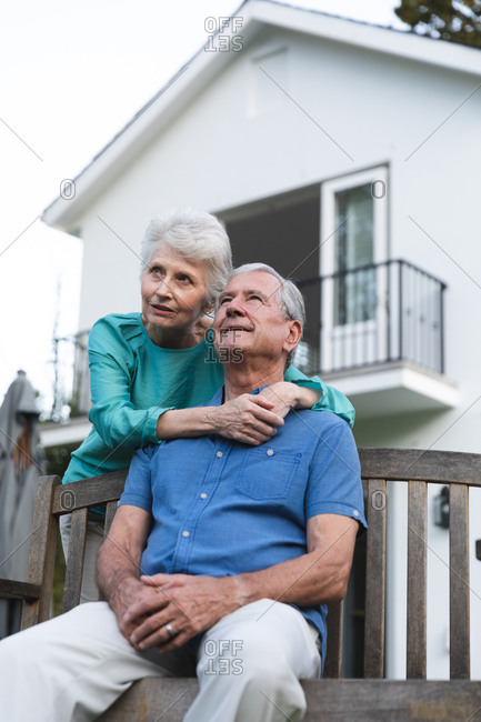Close up of a happy retired senior Caucasian couple at home in the garden outside their house, the man sitting on a bench and the woman standing behind embracing him, both looking away and smiling, at home together isolating during coronavirus covid19 pandemic