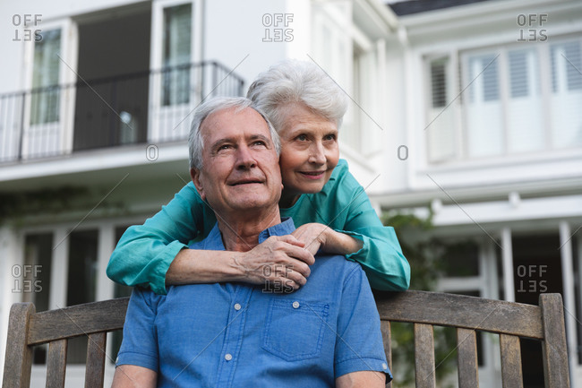 Happy retired senior Caucasian couple at home in the garden outside their house, the man sitting on a bench and the woman standing behind embracing him, both looking away and smiling, at home together isolating during coronavirus covid19 pandemic