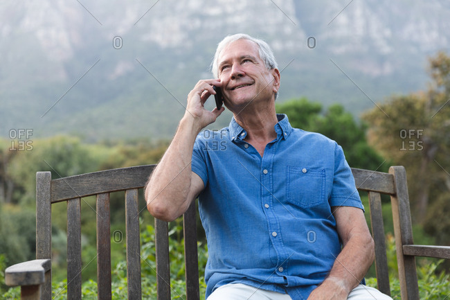 Happy retired senior Caucasian man at home in the garden outside his house, sitting on a bench, relaxing in nature and talking on a smartphone, looking away and smiling, self isolating during coronavirus covid19 pandemic