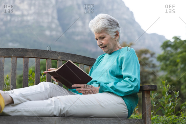 Happy retired senior Caucasian woman at home in the garden outside, sitting on a bench, reading a book with her legs up, relaxing in nature, self isolating during coronavirus covid19 pandemic