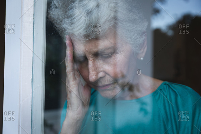 Retired senior Caucasian woman at home standing by the window with a headache, holding her head, with reflections of the garden in the window, self isolating during coronavirus covid19 pandemic