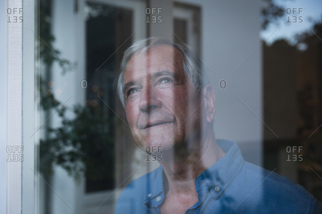 Happy retired senior Caucasian man at home looking out of the window smiling, with reflections of the garden in the window, self isolating during coronavirus covid19 pandemic