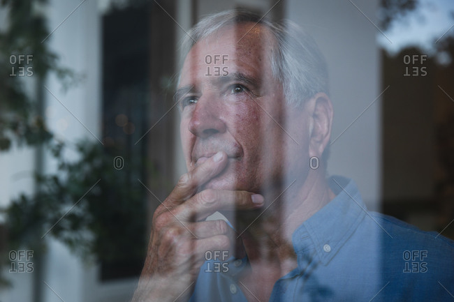Close up of a retired senior Caucasian man at home looking out of the window thinking holding his chin and looking away, with reflections of the garden in the window, self isolating during coronavirus covid19 pandemic