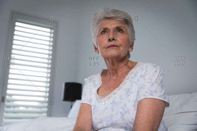 Close up of a retired senior Caucasian woman at home sitting up in bed in her nightclothes and looking away, self isolating during coronavirus covid19 pandemic