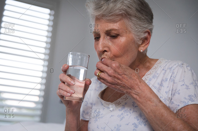 Close up of a retired senior Caucasian woman at home sitting up in bed in her bedroom holding a glass of water and taking medication, self isolating during coronavirus covid19 pandemic