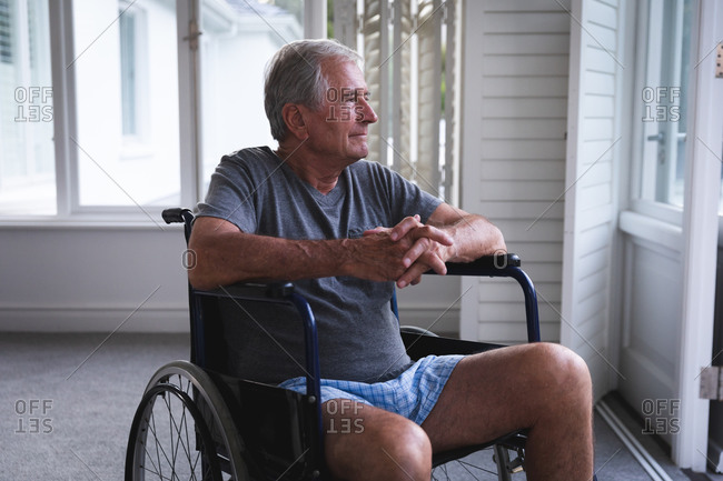 A retired senior Caucasian man at home, sitting in a wheelchair wearing underclothes in front of a window, on a sunny day looking away in thought, self isolating during coronavirus covid19 pandemic