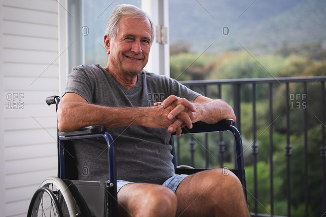 Portrait of retired senior Caucasian man at home, wearing underclothes sitting in a wheelchair in front of a window, on a sunny day looking to camera and smiling, self isolating during coronavirus covid19 pandemic