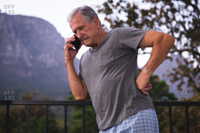A handsome senior Caucasian man enjoying his retirement, in a garden in the sun talking on a mobile phone, self isolating during coronavirus covid19 pandemic