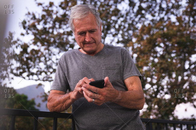 A handsome senior Caucasian man enjoying his retirement, in a garden in the sun text messaging with a mobile phone, self isolating during coronavirus covid19 pandemic