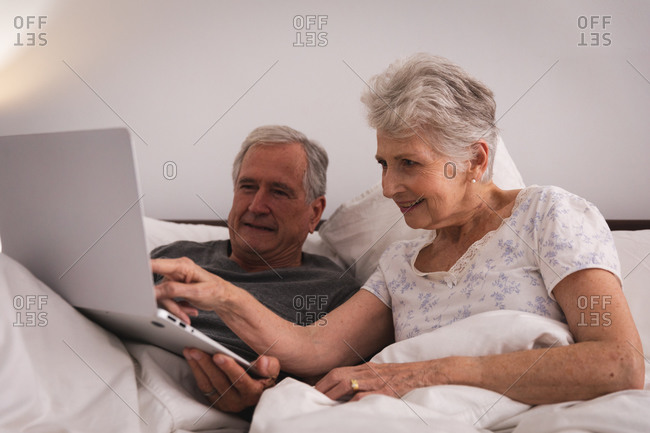 Close up of a happy retired senior Caucasian couple at home sitting up in bed in their bedroom, talking and using a laptop computer together and smiling, couple isolating during coronavirus covid19 pandemic