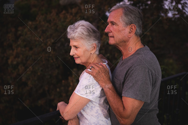 Side view of retired senior Caucasian couple at home in their garden, standing together, the man with his hand on the shoulder of the woman both looking away, at home together isolating during coronavirus covid19 pandemic
