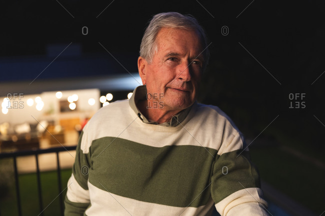 Portrait of a handsome senior Caucasian man enjoying his retirement, standing outside his house on a balcony in the evening looking away smiling, self isolating during coronavirus covid19 pandemic
