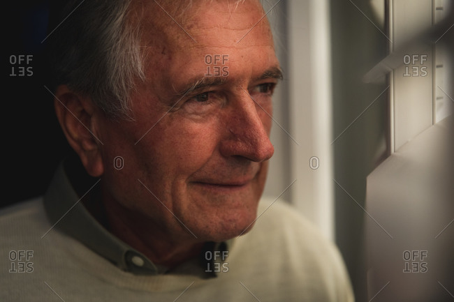 Close up of a handsome senior Caucasian man enjoying his retirement, standing at home looking out of a window and smiling in the evening, self isolating during coronavirus covid19 pandemic
