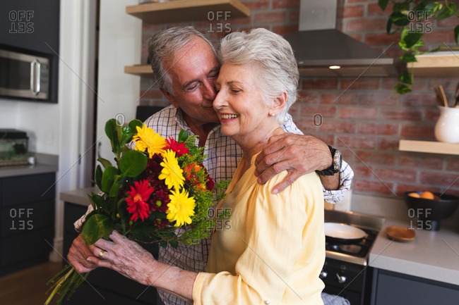 A senior Caucasian couple enjoying their retirement, standing in their kitchen on a sunny day, the man presenting the woman with a bouquet of flowers and kissing her on the cheek, at home together isolating during coronavirus covid19 pandemic