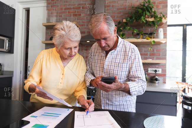 A retired senior Caucasian couple standing at a table in their dining room looking at paperwork, using a calculator and discussing their finances, at home together isolating during coronavirus covid19 pandemic