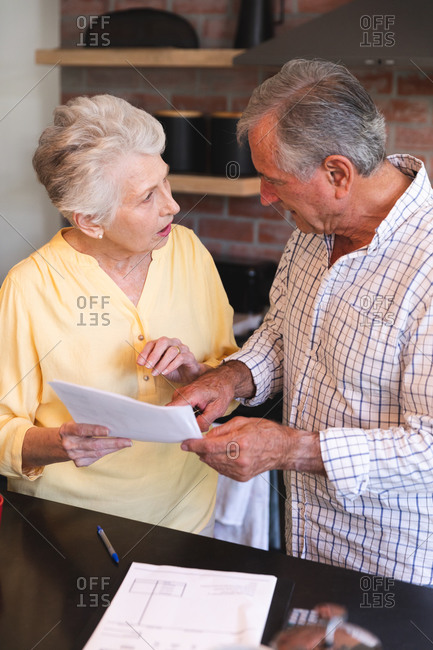 Close up of a retired senior Caucasian couple standing at a table in their dining room looking at paperwork and discussing their finances, at home together isolating during coronavirus covid19 pandemic