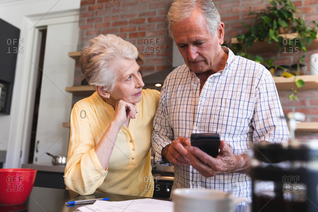 A retired senior Caucasian couple standing at a table in their dining room using a calculator and discussing their finances, with a pot of coffee and cup on the table in the foreground, at home together isolating during coronavirus covid19 pandemic