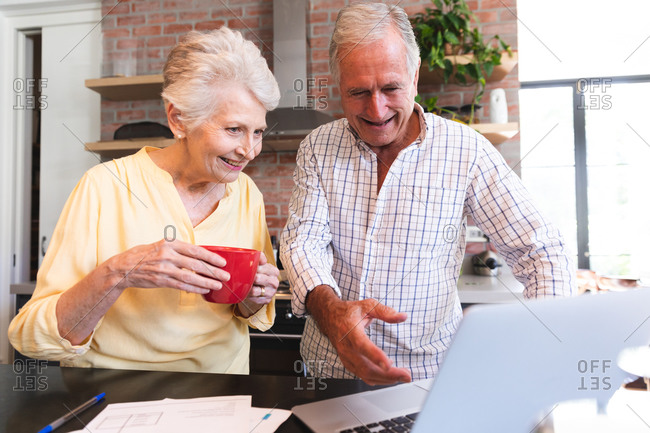 A retired senior Caucasian couple at home standing at a table in their kitchen, talking and smiling, using a laptop computer together, couple isolating during coronavirus covid19 pandemic