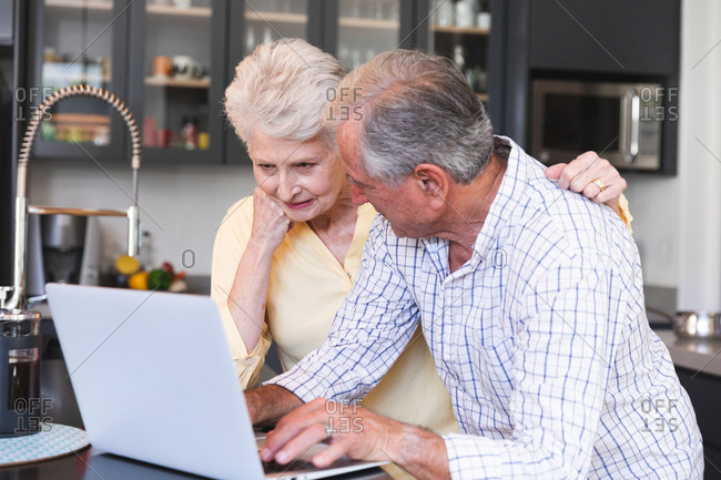 A retired senior Caucasian couple at home standing at the worktop in their kitchen, talking and smiling, using a laptop computer together, the woman with her arm around the man, couple isolating during coronavirus covid19 pandemic
