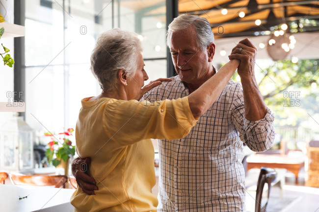 Happy retired senior Caucasian couple at home holding hands, dancing together in their kitchen and smiling, at home together isolating during coronavirus covid19 pandemic