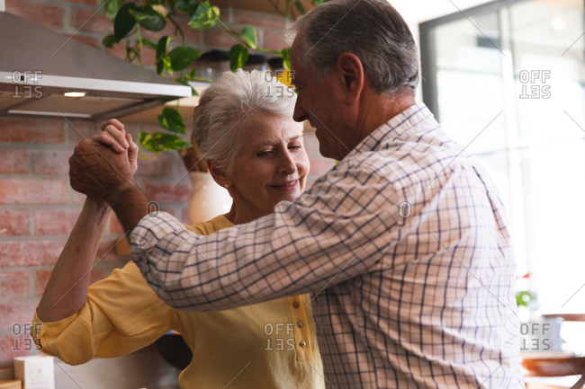 Close up of happy retired senior Caucasian couple at home holding hands, dancing together in their kitchen and smiling, at home together isolating during coronavirus covid19 pandemic