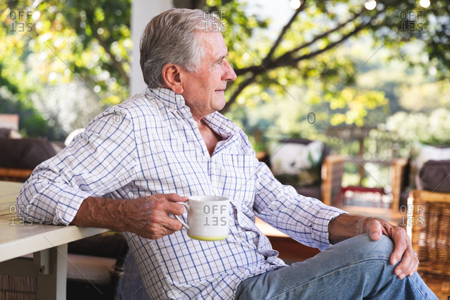 Side view of a happy retired senior Caucasian man at home in the garden outside his house on a sunny day, sitting on a bench, holding a cup of coffee, looking away and smiling, self isolating during coronavirus covid19 pandemic