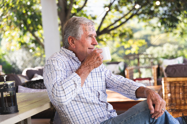 Side view of a happy retired senior Caucasian man at home in the garden outside his house on a sunny day, sitting on a bench and drinking a cup of coffee, looking away and smiling, self isolating during coronavirus covid19 pandemic