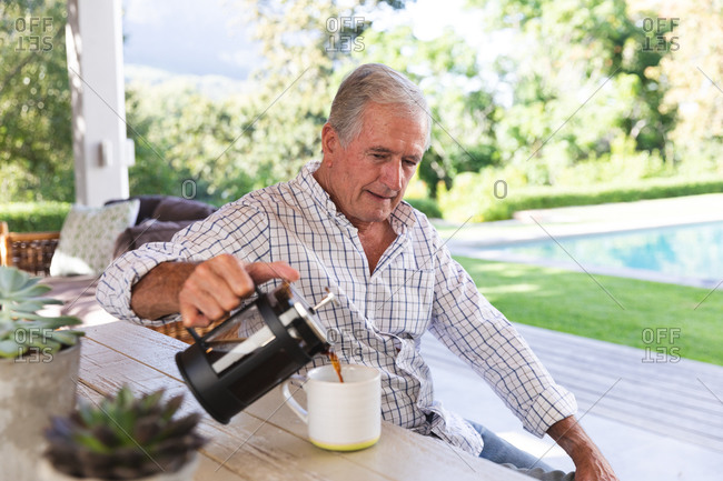 Side view of a happy retired senior Caucasian man at home in the garden outside his house on a sunny day, sitting on a bench at a table and pouring a cup of coffee and smiling, self isolating during coronavirus covid19 pandemic