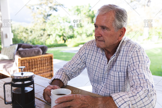 Happy retired senior Caucasian man at home in the garden outside his house on a sunny day, sitting on a bench, holding a cup of coffee, looking away and smiling, self isolating during coronavirus covid19 pandemic