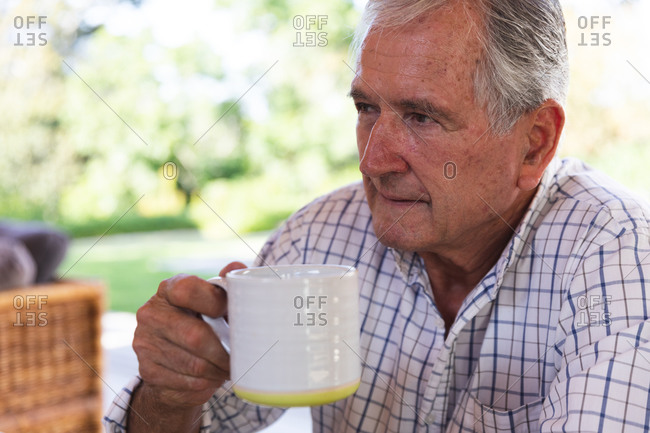 Close up of a happy retired senior Caucasian man at home in the garden outside his house on a sunny day, sitting on a bench, holding a cup of coffee, looking away and smiling, self isolating during coronavirus covid19 pandemic