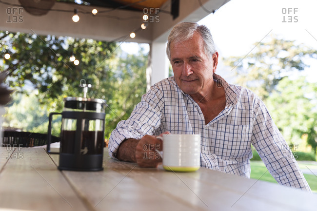 Happy retired senior Caucasian man at home in the garden outside his house on a sunny day, sitting at a table with a pot of coffee, holding a cup, looking away and smiling, self isolating during coronavirus covid19 pandemic